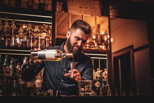 барман прави коктейли с добро барово оборудване