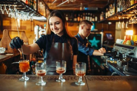 барманка използва бар аксесоари за да направи свежи коктейли