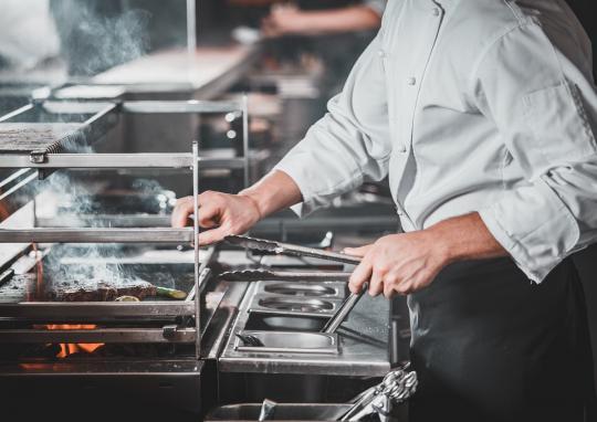 готвач в професионална кухня готви с гастронорми